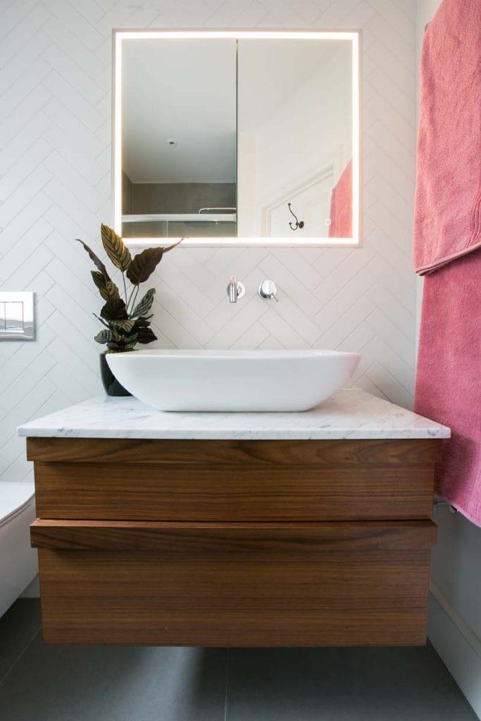 Bespoke walnut bathroom vanity Ealing with white herringbone wall tiles.