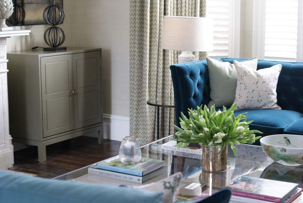 Tom Faulkner glass coffee table with blue velvet sofa