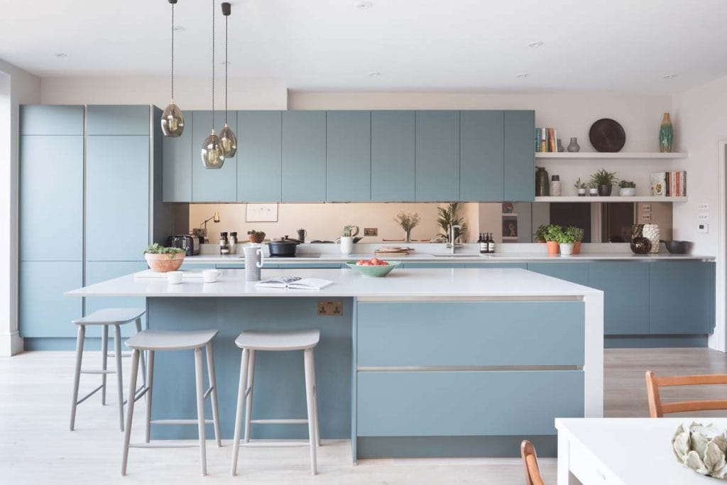 Blue handless contemporary kitchen Ealing with grey bar stools