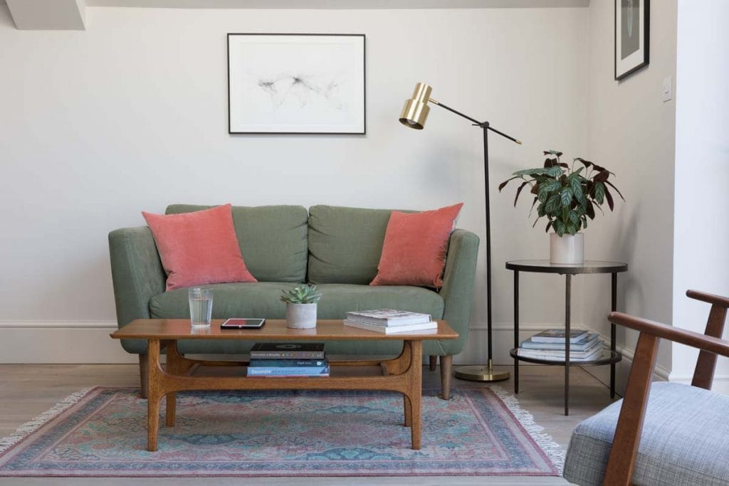 Green wool sofa Ealing with coral cushion and mid century black and brass floor lamp