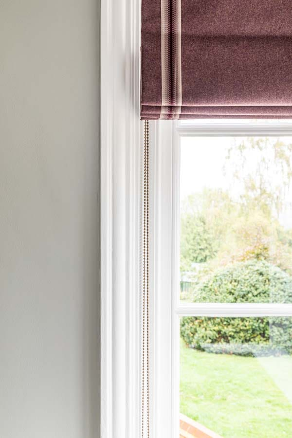 Aubergine wool blind with striped aubergine trim.