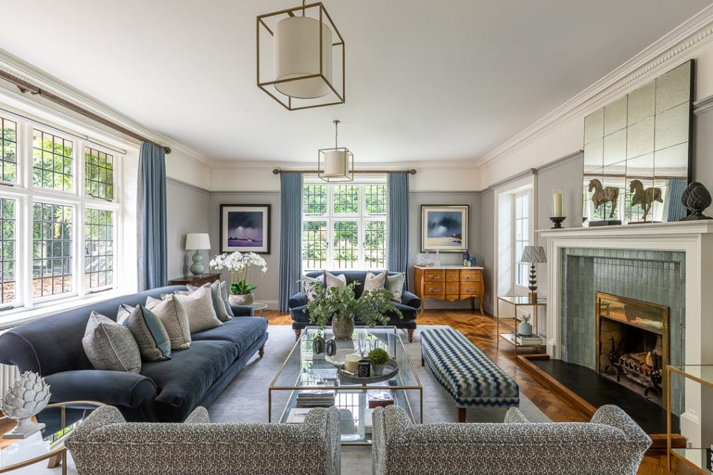 Arts and Crafts drawing room with soft colour scheme of greys and blues, brass and glass Tom Faulkner coffee table, upholstered bench and parquet flooring.