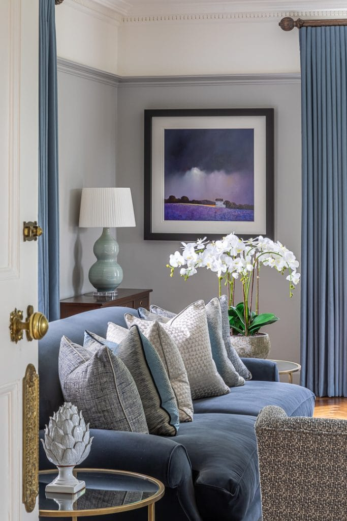Grey velvet sofa with bespoke cushions, blue wool curtains and potted iris in the background.