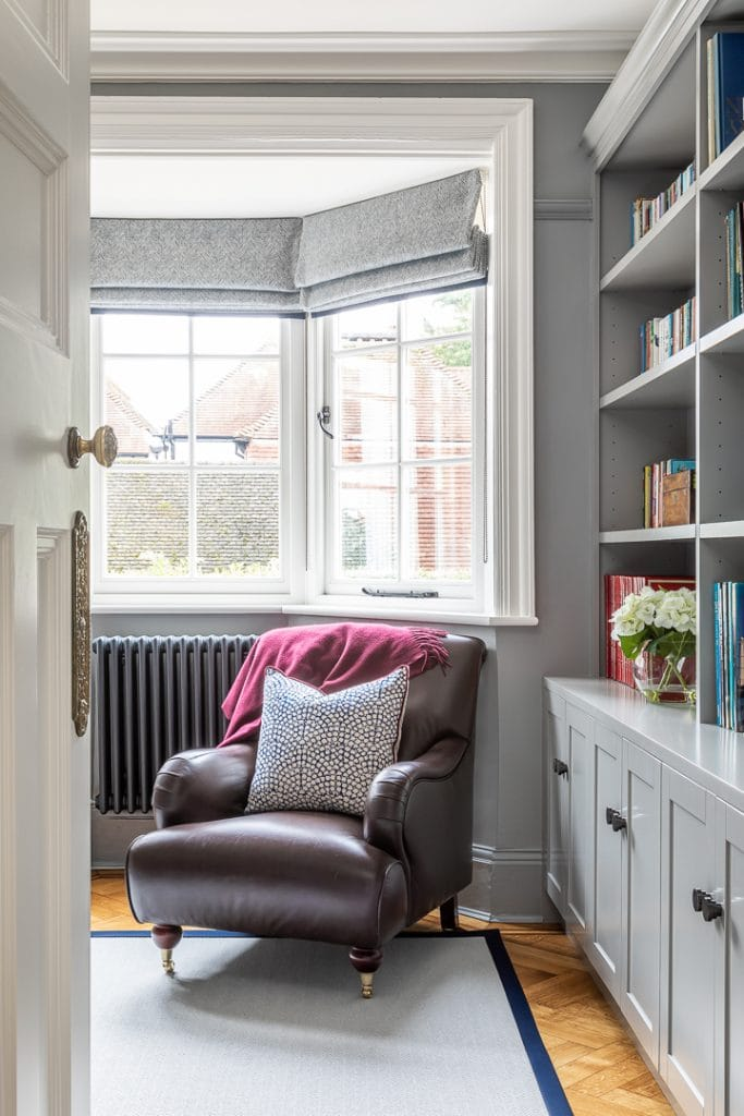 Grey painted study with bespoke book shelves with dark bronze handles. Leather armchair with aubergine throw.