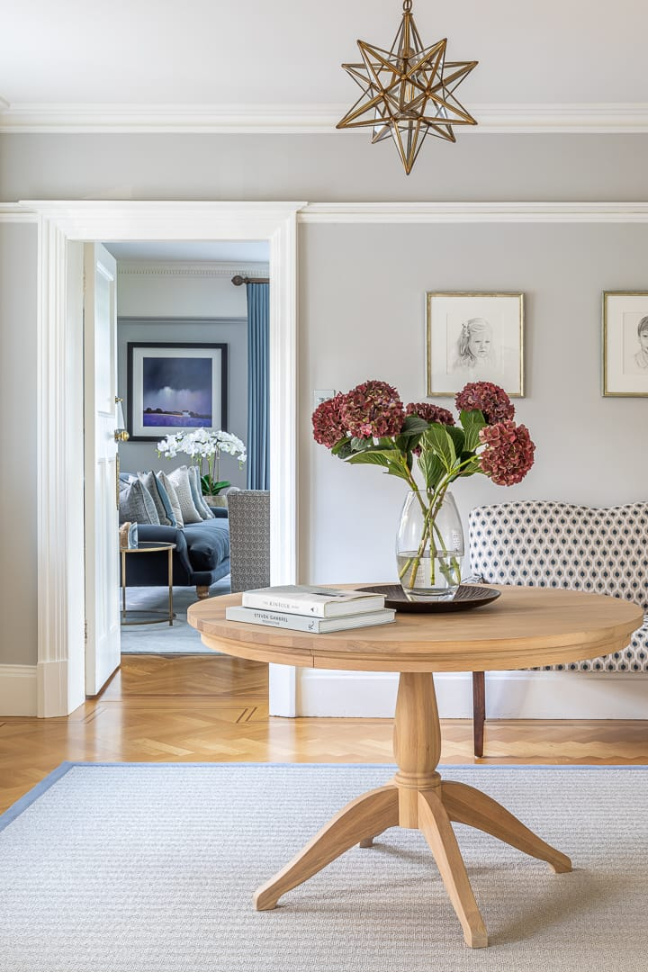 Large airy hallway with round oak circular table, upholstered sofa and herringbone rug with views into formal drawing room.