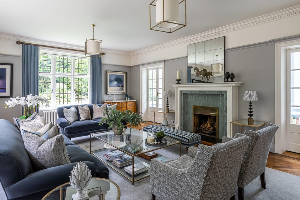 Formal drawing room with blue and grey colour scheme, brass and glass coffee table, two grey velvet sofas and pair of upholstered chairs. Large duck egg blue tiled fire place with black framed mirror above.