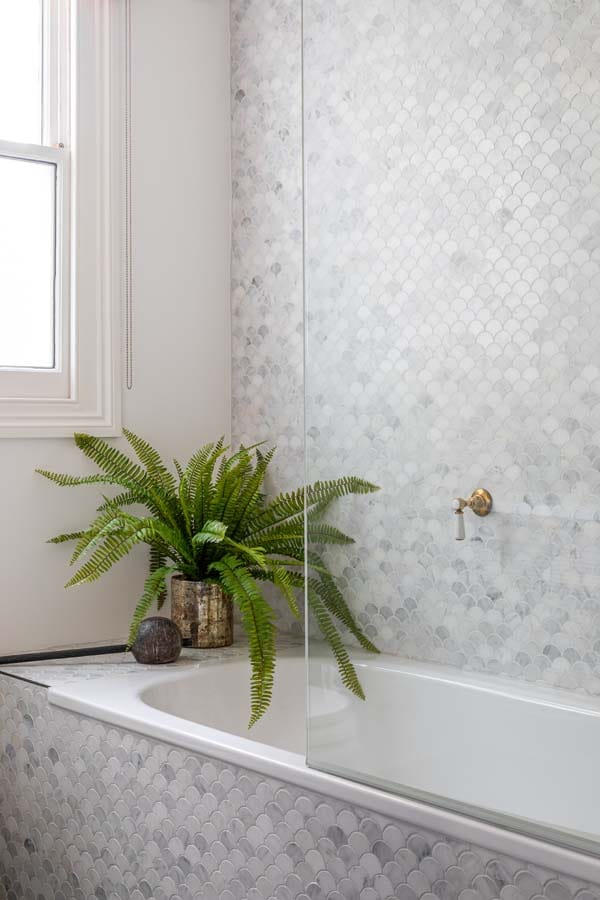 Bath showing marble scalloped tiled wall.