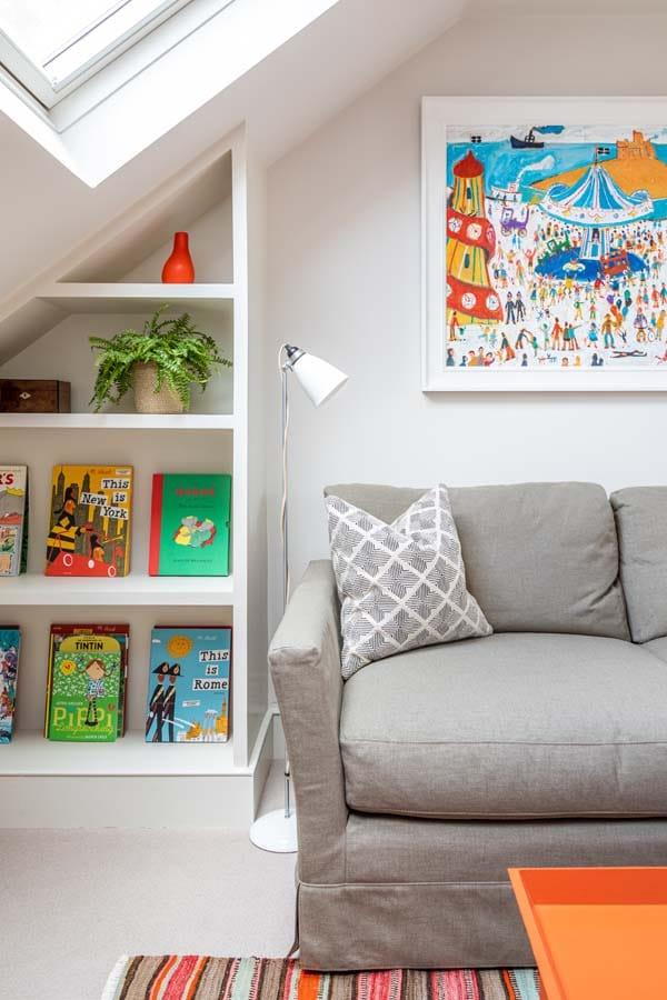 Playroom with bespoke book case, sofa from sofa.com and brightly coloured artwork depicting a fun fair.