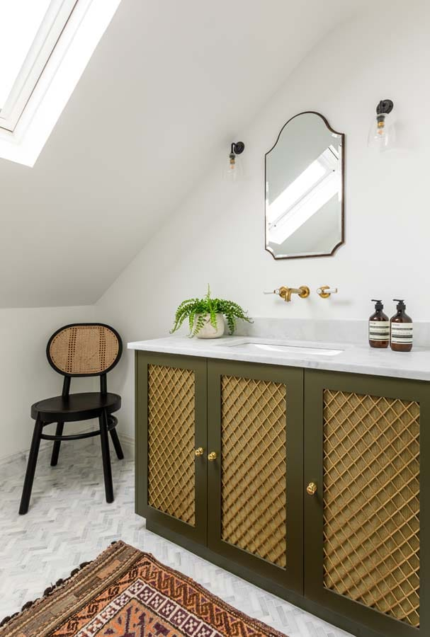 Olive green bespoke vanity with brass grill, marble top and brass taps sitting on a marble herringbone tiled floor.