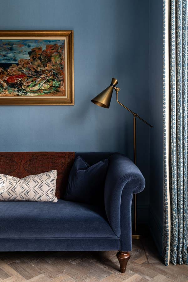 Blue mohair velvet sofa with colourful fish oil painting on blue linen walls.