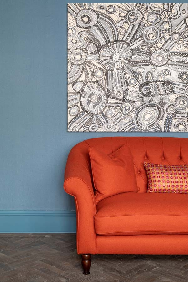 Bright red sofa under aboriginal artwork set against blue linen wallpaper.