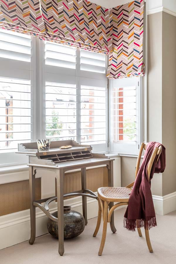 Small dressing table sitting in bay window with multi coloured zig zag stitched roman blinds.