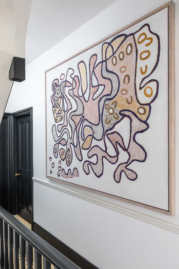 Large abstract aboriginal artwork with white walls and black painted doors on landing.