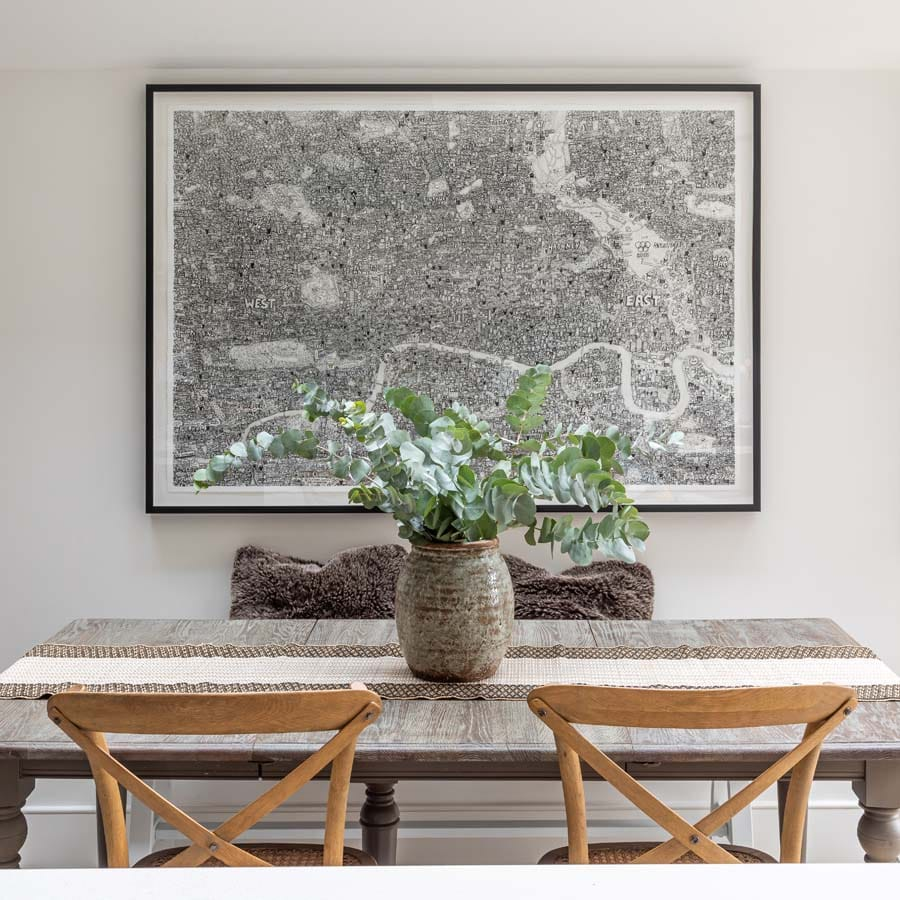 Oak kitchen table sitting under large map of London.