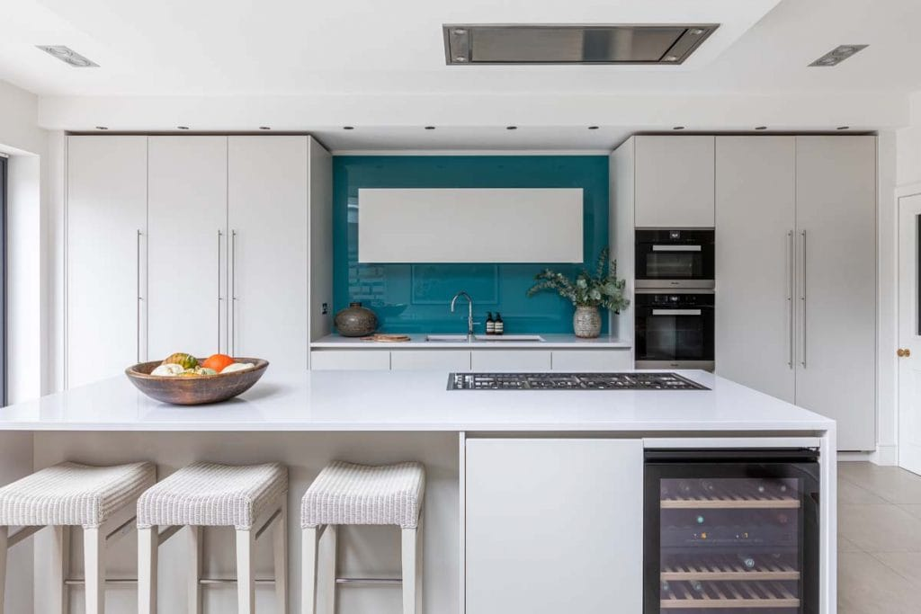 Contemporary white handleless kitchen with large island and turquoise splash back.