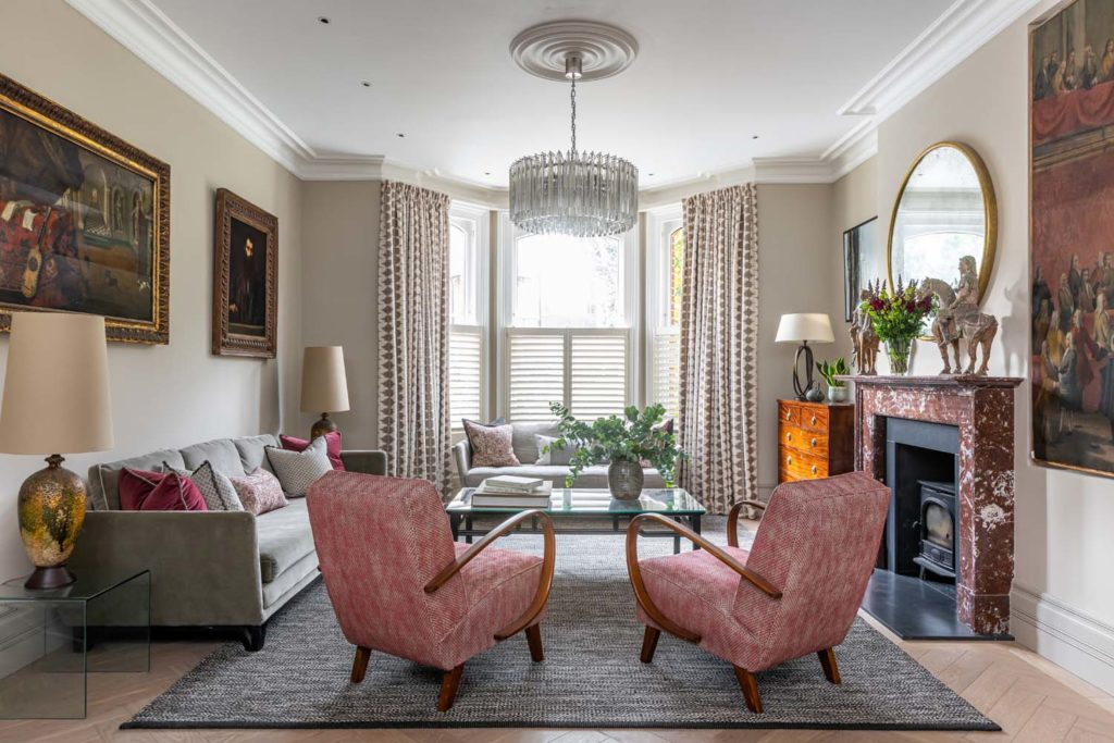 Reception room with 2 red upholstered mid century chairs, Fiona McDonald mid century oversized lamps, bespoke Sinclair Till rug, Reid & Wright mirror,