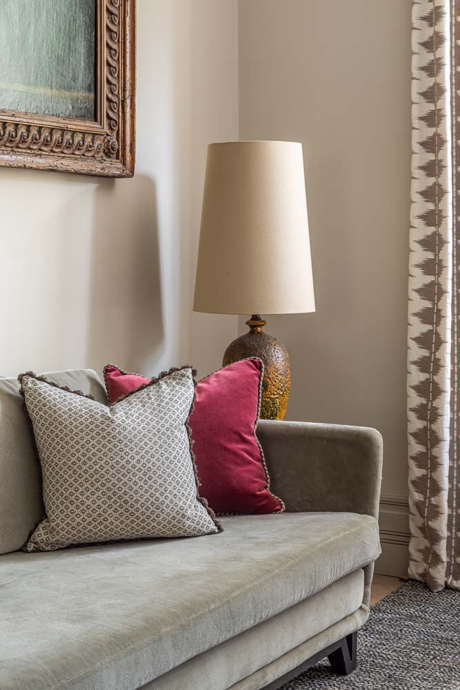 Green velvet sofa with decorative cushions and large oversized Fiona McDonald lamp and curtain detail.