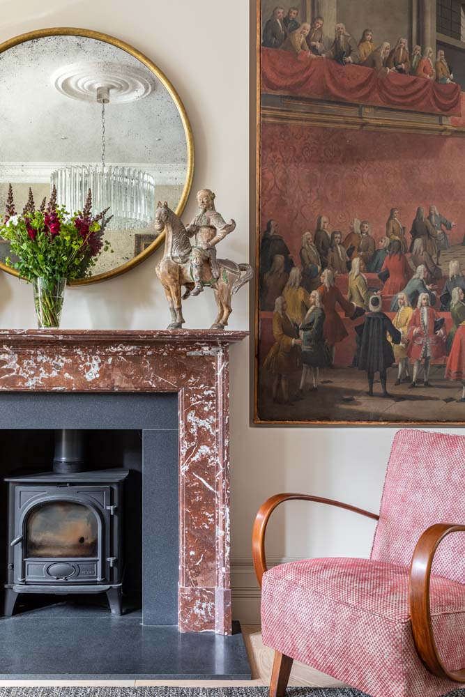 Reid & Wright gilt mirror, red marble fireplace, antique artwork and mid century armchair covered in red Nina Campbell fabric