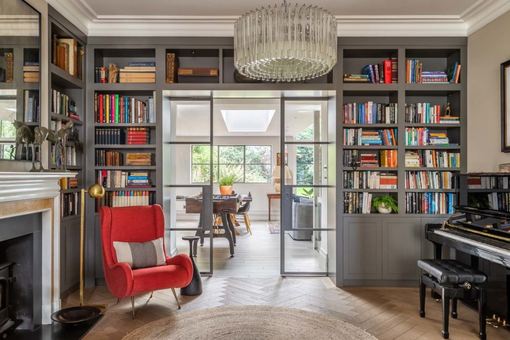 Bespoke library joinery, red Fiona McDonald chair, crittal sliding doors, piano.