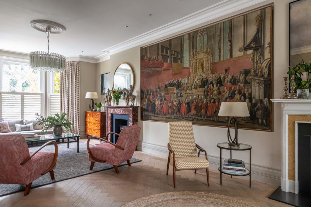 Large antique artwork, view of front of sitting room with red mid century armchairs and yellow zig zag armchair.