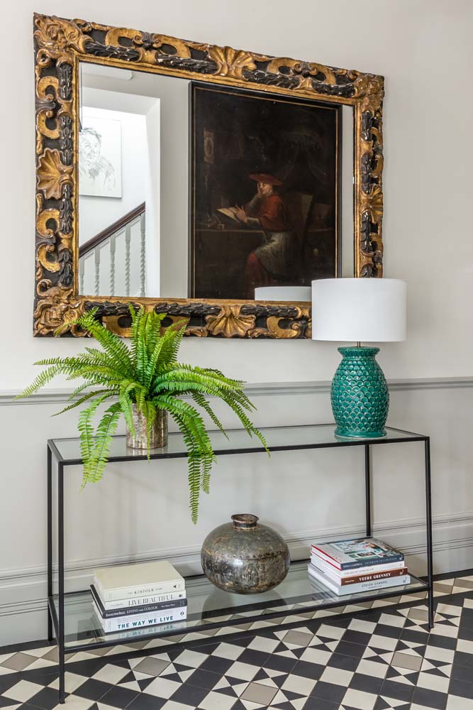 Black and gilt mirror, Tom Faulkner bronze and glass console, turquoise Soho House lamp, green fern.