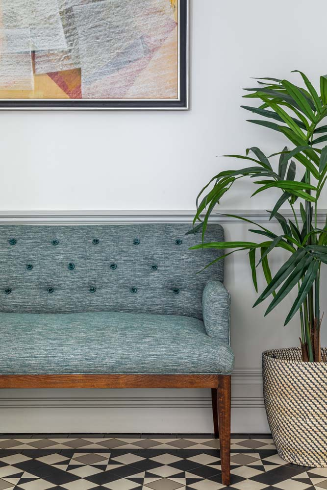 David Seyfried button back sofa, large fern plant, yellow and white artwork, tessellated flooring.