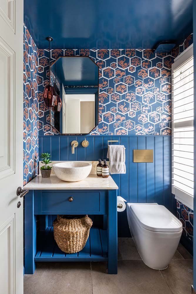 Farrow & Ball Stifkey Blue tongue & groove joinery with Farrow & Ball wallpaper and blue painted gloss ceiling. Rothschild & Bicker orange glass pendant, marble topped vanity.