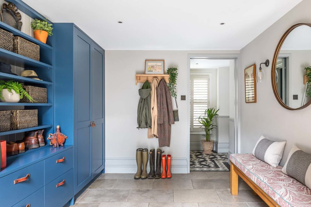 Bespoke Farrow & Ball Stifkey Blue boot room joinery, bench with Fermoie seat pad and Cox and Cox mirror and Fritz Fryer Wall lights