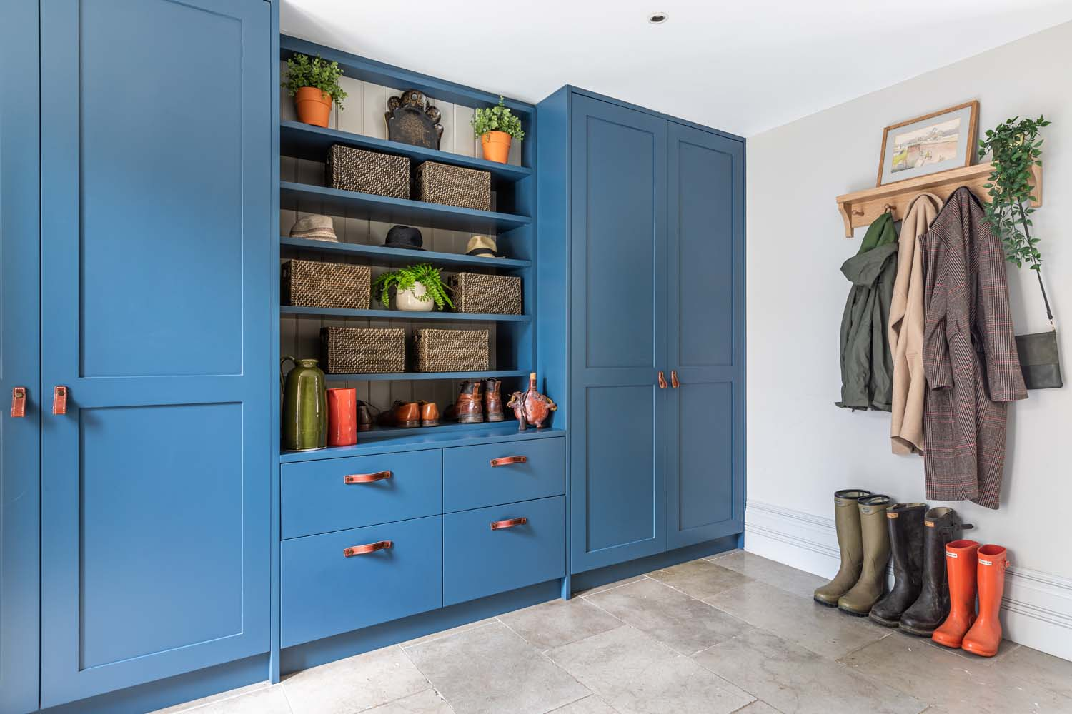Bespoke boot room joinery in Farrow & Ball Stifkey Blue, wooden coat rack with coats and wellington boots, limestone floor